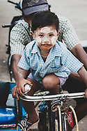 Mawlamyine, Myanmar - October 26, 2011: A boy sits in front of his father peddling a rickshaw in Mawlamyine, formerly called Moulmein. The city is the fourth largest in Myanmar and is also the capital of Mon State.