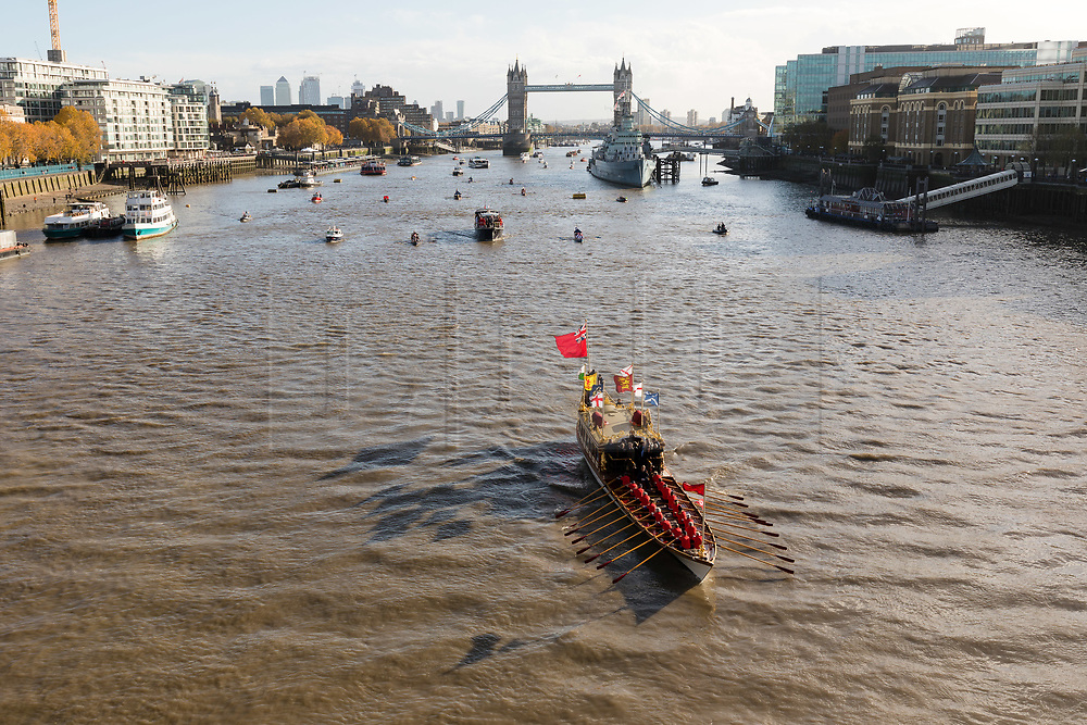 © Licensed to London News Pictures. 11/11/2018. London, UK.  A flotilla of boats including the Royal barge, QRB Gloriana (leading), the Havengore and traditional boats travel up the River Thames in front of Tower Bridge towards the Houses of Parliament in Westminster for a remembrance service, led by the Havengore, as part of Armistice Day centenary events taking place in central London. Big Ben will strike at 11am to mark the start of the two minutes silence and the Havengore will sound her horn to signify the end of the two minutes silence in central London.  Photo credit: Vickie Flores/LNP