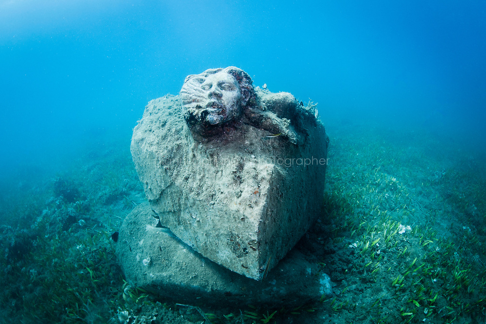 """TALAMONE, ITALY - 27 AUGUST 2019: """"Acqua"""", a carved piece of Carrara marble by artist Giorgio Butini, is seen here 8 meters underwater in Talamone, Italy, on August 27th 2019.<br /> <br /> In 2006, fisherman Paolo Fanciulli used government funds and the donations from his loyal excursion clients to fund a project in which they protected the local waters from trawling by dropping hundreds of concrete blocks around the seabed. But his true dream was to lay down works of art down on the sea floor off the coast of Tuscany. His underwater art dreams came true when the owner of a Carrara quarry, inspired by Mr. Fanciulli's vision, donated a hundred marble blocks to the project.<br /> Mr. Fanciulli invited sculptors to work the marble and set up kickstarter accounts, boat tours and dinners to fund the project. The acclaimed British artist Emily Young carved a ten-ton """"Weeping Guardian"""" face, which was lowered with other sculptures into the water in 2015.<br /> Since then, coral and plant life have covered the sculptures and helped bring back the fish. And Paolo the Fisherman is catching as many of them as he can."""