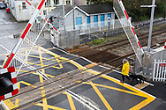 Woman in yellow coat walking a black dog starts to cross a railway level crossing as the barriers go up / are raised