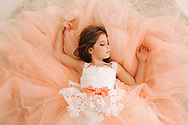 Photo of little girl in studio. Little beautiful girl with brown hair in a Peach-colored dress.