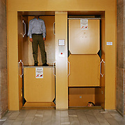 Workers travelling on an old fashioned elevator , in a local government finance office in Berlin , taken on the 28th of February 2008. From the series Desk Job, a project which explores globalisation through office life around the World.