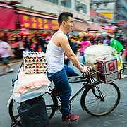 Man delivering goods on bicycle at Bowrington Road wet market, Hong Kong