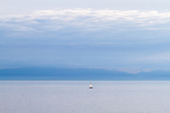 A small sailing boat (a Hunter 280) in the Salish Sea (Georgia Straight) west of Vancouver.  Photographed from Juniper Point at  Lighthouse Park in West Vancouver, British Columbia, Canada. The mountains in the background are located on Vancouver Island.
