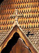 """Detail of wooden cross and shingles. Heddal stave church is Norway's largest stave church. This triple nave stave church, which some call """"a Gothic cathedral in wood,"""" was built in the early 13th century and restored in 1849-1851 and the 1950s. Heddal stavkirke is in Notodden municipality, Telemark County, Norway."""