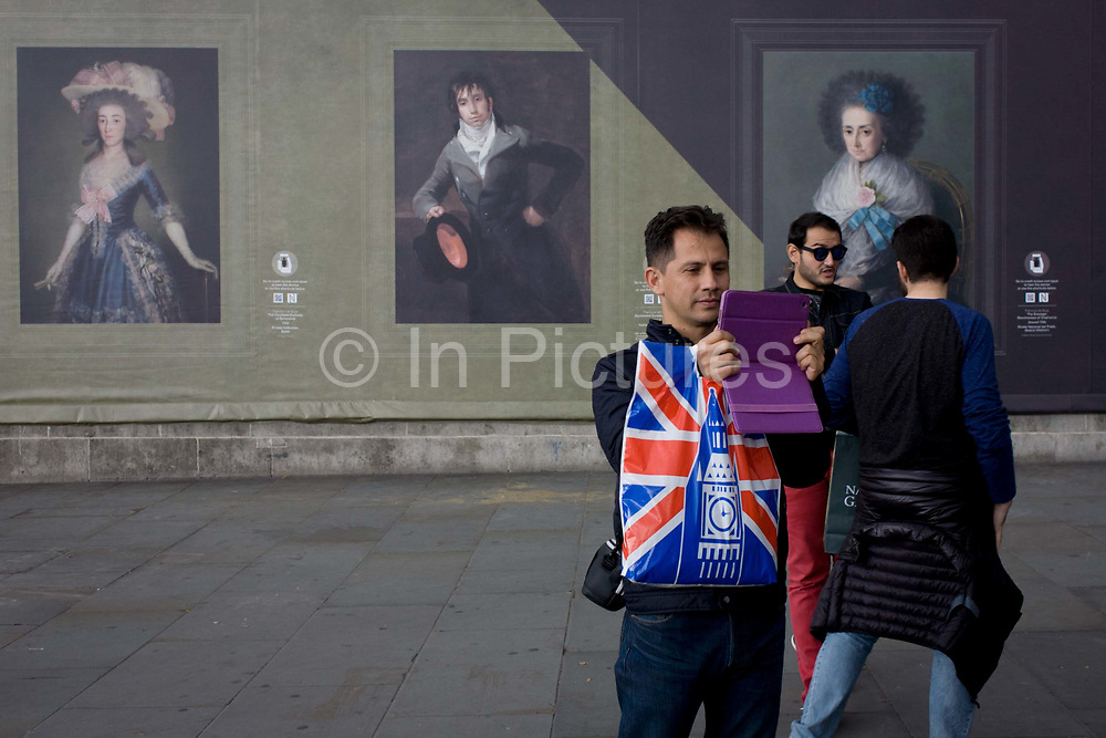 A tourist to Britain takes a photo with a modern handheld device near potraits by the Spanish romantic artist Francesco Goya, sponsored by Credit Suisse and advertised on a construction hoarding outside the National Portrait Gallery. The portraits are from the left: Countess-Duchess of Benavente; Bartolome Sureda y Miserol and The Dowager Marchioness of Villafranca. Paintings by Goya are exhibited inside the National Gallery next door and while a large grey hoarding is in place during works in Trafalgar Square, some of Goya's work is reproduced to viewers outside. Tourists to this central landmark in the capital stop and take photos and this selfie girl faces the Goya but seemingly ignores the high art in favour of a fleeting moment with her smartphone - symbolising the disposable and unthinking nature of tourism and travel.