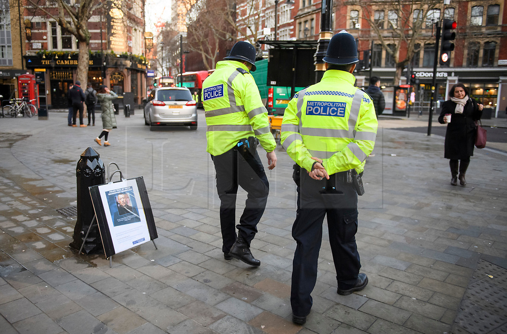 © Licensed to London News Pictures. 17/12/2018. London, UK.  Police officers walk past a notice explaining that facial recognition trials are taking place in the area. Members of the Metropolitan police trial facial recognition technology on members of the public in central London. The surveillance software is being used overtly with a uniformed presence. Privacy campaigners have expressed concerns about the use of the technology. Photo credit: Ben Cawthra/LNP