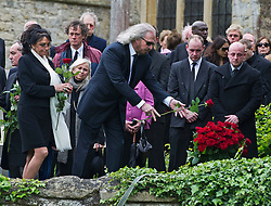 © London News Pictures. 08/06/2012. Thame, UK.  Barry Gibb, brother of Robin Gibb throwing a rose on to the coffin of his brother Robin Gibb during a burial at St Mary's Church in Thame, Oxfordshire  on June 8, 2012. Robin Gibb died on May 20, 2012 aged 62 following a long battle against cancer. Photo credit: Ben Cawthra/LNP
