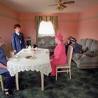 Queen Elizabeth II joins Mrs Susan McCarron (front left) her ten-year-old son, James (hidden behind Queen), and Housing Manager Liz McGinniss for tea in their home in the Castlemilk area of Glasgow.