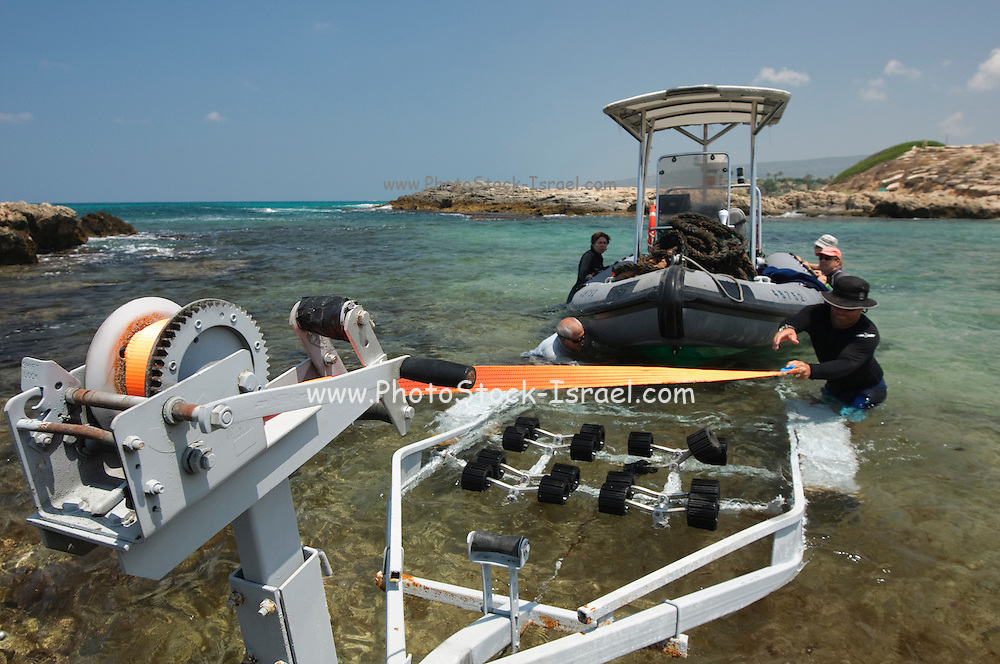 A RIB (Rigid hulled) inflatable boat is lowered into the Mediterranean sea