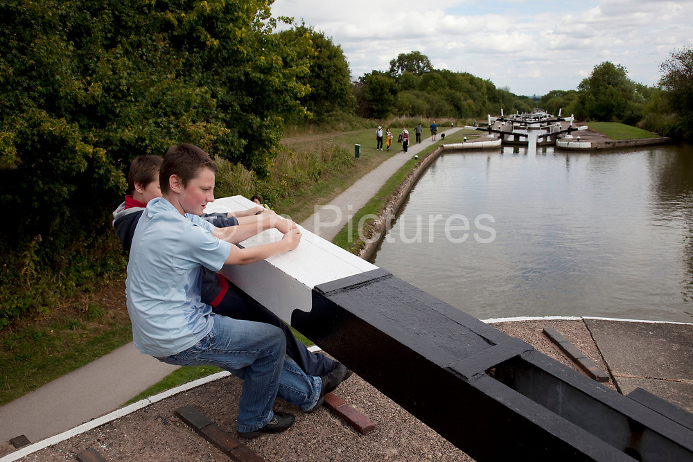 Two boys close a lock on the Grand Union Canal at Hatton in Warwickshire. This flight of locks is 2.5 miles long and has 21 locks.