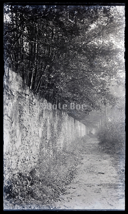 path beside a very long wall in the woods circa 1920s