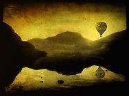 A hot air balloon in flight over lakes and mountains