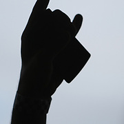 A silhouette of a hand with cell phone during the Rockstar Energy Uproar festival at the 1-800-Ask-Gary amphitheater in Tampa, Florida on Thursday, September 13, 2012. (AP Photo/Alex Menendez)