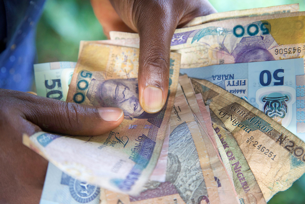 INDIVIDUAL(S) PHOTOGRAPHED: N/A. LOCATION: Calabar, Cross River, Nigeria. CAPTION: A close-up of local currency, Naira bills, illustrating the economic exchanges within Nigeria's health sector.
