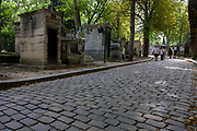 "Wide cobbled avenue in the Pere Lachaise cemetery, Paris. Père Lachaise Cemetery (Cimetière du Père-Lachaise) is the largest cemetery in the city of Paris, France (44 hectares (110 acres) though there are larger cemeteries in the city's suburbs. Père Lachaise is in the 20th arrondissement, and is reputed to be the world's most visited cemetery, attracting hundreds of thousands of visitors annually to the graves of those who have enhanced French life over the past 200 years. It is also the site of three World War I memorials. Père Lachaise Cemetery (French: Cimetière du Père-Lachaise- or officially cimetière de l'Est, ""East Cemetery"") is the largest cemetery in the city of Paris, France (44 hectares (110 acres) containing the remains of a million French and foreign dead."