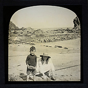 Magic lantern slide two children playing on a sandy beach circa 1900 location not known, presumed to be England, UK perhaps Cornwall