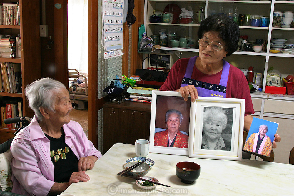 """(MODEL RELEASED IMAGE). Tama Matsuda, 100 years old, watches as her daughter-in-law Keiko, 75, proudly shows images of Tama at different ages. (Supporting image from the project Hungry Planet: What the World Eats). The Matsuda family is one of the thirty families featured in the book Hungry Planet: What the World Eats (p. 186). Hara hachi bu """"eat only until 80 percent full,"""" say older Okinawans. The island has been the focus in recent years of researchers trying to discover why a disproportionately large number of Okinawans are living to age 100 or more."""