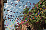 Paper fiesta banners called papel picado against a blue sky and classic colonial building along Calle Quebrada in the historic district of San Miguel de Allende, Mexico.