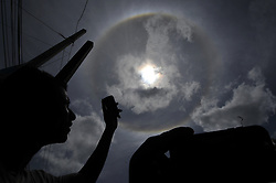 August 5, 2017 - Kathmandu, Nepal - Nepalese people taking photos using mobile photos as a 22° halo surrounded the sun as it shined on Kathmandu, Nepal on Saturday, August 5, 2017. The phenomenon, appearing as sunlight refracts in millions of ice crystals suspended in Earth's atmosphere, dazzles onlookers and provides bountiful photographic opportunities. (Credit Image: © Narayan Maharjan/NurPhoto via ZUMA Press)