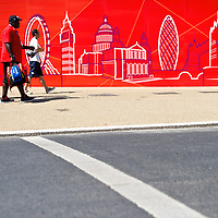 Athletes walk the grounds of the Olympic Village, with a mural depicting the city sky line, during the 2012 London Summer Olympics.