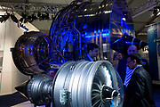 Potential buyers discuss Trent engines with Rolls-Royce employee at the Farnborough Air Show. In one of the main halls where manufacturers and exhibitors showcase their products for the defence and aerospace industries, a RR employee discusses the technical merits of the Trent family turbofans whose orders help preserve jobs at the company factories. The Farnborough International Airshow is a seven-day international trade fair for the aerospace industry and held every two years in mid-July at Farnborough Airport in Hampshire, England known as the home of British aviation, held since there since 1948. The show is usually attended by more than 1,300 exhibitors and 150,000 trade visitors.