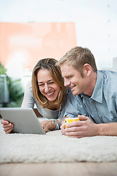 Couple lying on floor with digital tablet