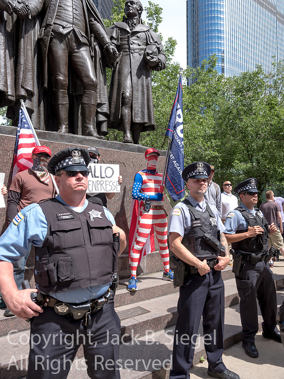 Three members of the Chicago Police Department protect anti-Sharia law protesters by forming a human barricade