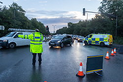 Licensed to London News Pictures. 05/10/2021. London, UK. Police direct cars away from the A3  Kingston Bypass, South West London which was closed due to severe flooding last night.  The A3 was closed this morning after rain caused flooding on the carriage way as traffic built up on surrounding roads. Torrential rain last night has caused severe flooding in London with many roads blocked with flood water and broken down cars. Photo credit: Alex Lentati/LNP