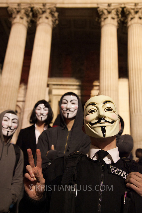 Masked up members of Anonymous in front of the cathedral.  The London Stock Exchange was attempted occypied in solidarity with Occupy Wall in Street in New York and in protest againts the economic climate, blamed by many on the banks. Police managed to keep people away fro the Patornoster Sqaure and the Stcok Exchange and thousands of protestors stayid in St. Paul's Square, outside St Paul's Cathedral. Many camped getting ready to spend the night in the square.
