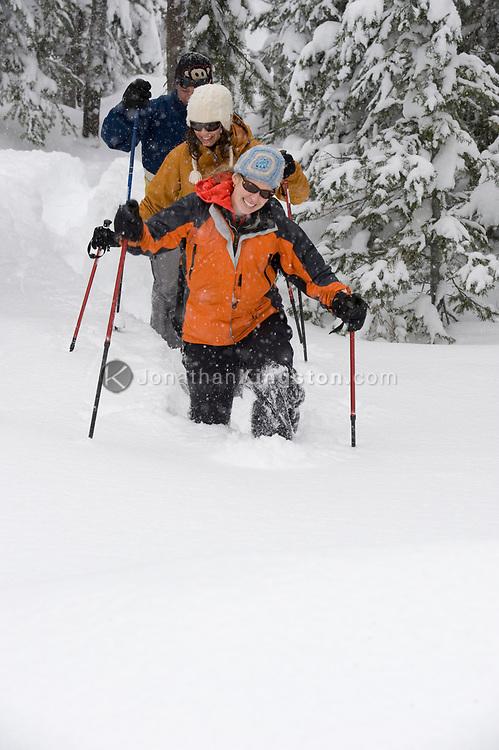 Front view of three people snowshoeing in the woods in deep powder in Bend, Oregon. (releasecode: jk_mr1033, jk_mr1035, jk_mr1034) (Model Released)