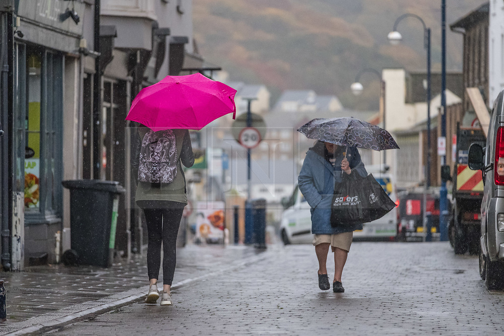© Licensed to London News Pictures. Aberystwyth, UK. 7/11/2018. People walking in the rain on a very wet, but mild morning in Aberystwyth. The Met Office has issued a yellow warning for rain and floods covering much of south and west Wales this morning, with a further warning for more rain and gale force winds issued for the same area on Friday. Photo credit: Keith Morris/LNP.