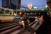 Een vrouw wacht geduldig tot ze kan oversteken, terwijl het verkeer voorbij raast en er een trein op de achtergrond rijdt.