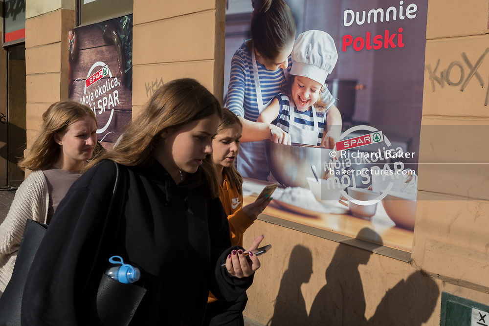 Young modern Polish women walk past a poster outside a Spar supermarket showing the stereotyping of gender: a mother and her daughter enjoying baking in the kitchen together, on 23rd September 2019, in Krakow, Malopolska, Poland. The poster translates as: 'My neighborhood ,my spar'.