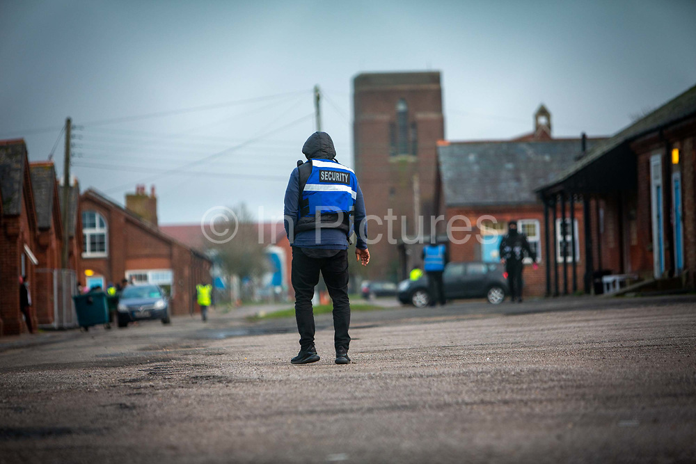 Private security guards patrol the barracks patrol over Asylum seekers inside Napier Barracks on the 5th of February 2021, Folkestone Kent. Over 400 asylum seekers are being kept at Napier Barracks in unsuitable, cold accommodation, they are experiencing mental health issues as well as being vulnerable to health conditions including COVID-19. 3 people living inside the barracks have attempted suicide in 2021 already.