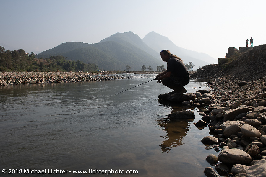 Round the World Doug Wothke pulled out his rod during a stop along the Trishuli River on day-10 of our Himalayan Heroes adventure  riding from Nuwakot back to Kathmandu, Nepal. Thursday, November 15, 2018. Photography ©2018 Michael Lichter.
