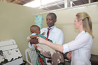 Senior Clinical Officer Jones Mwamba holding a malnourished child with Gabby Logan at Metero Refferal Clinic in Lusaka, Zambia on Wednesday 12 November 2014.<br /> <br /> <br /> <br /> <br /> At the Metero Reference Clinic in Lusaka.
