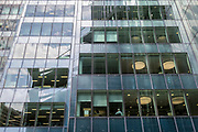 A businessman sits with his back to the window on a lower floor of his corporate office building in the City of London, the capital's financial district - aka the Square Mile, on 8th August, in London, England.