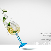 A Bombay Sapphire Laverstoke drink photographed spilling out of the glass and splashing the ingredients into the air. Photographed in the Hype creative photography studio, Basingstoke Hampshire.