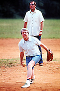 Jimmy Carter plays softball in his hometown of Plains, Georgia. Carter was pitcher and captain of his team that was comprised of off duty U.S. Secret service agents and White House staffers. The opposing team was comprised of members of the White house traveling press and captained by Billy Carter, the president's brother. In the background is US Secret Service Agent Charles Zaboril, Carter's lead agent. Zaboril was a young agent scheduled to be on the back of President John F. Kennedy's limousine on the day he was assassinated in Dallas, Texas.- To license this image, click on the shopping cart below -