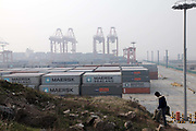 A farmer carries a heavy load up a small hill near the Yangshan Deepwater Container Port in Shanghai, China on 25 January 2010.  Shanghai is now the world's busiest port in terms of container volume.