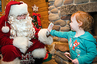 Alex Kaye, 2, of Knoxville, Tenn., gets a high-five from Santa Claus while visiting jolly elf at the Town Square.