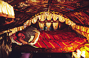 Leslie asleep in bed. Romany gypsies, Leslie and Edna traveling with a traditional bowtop wagon in the English countryside...English Romany Gypsies traditionally traveled the country roads camping nearby towns and villages, choosing the grassy roadside banks, where they tethered their horses, or in farmer's fields, when they were allowed. Travelling in bowtop wagons drawn by horses, and before that with tents, sometimes with horse drawn carts or just by foot. Often they worked as casual agricultural labourers, doing the seasons work. They also could earn their living in different ways, sometimes selling their wares, brass, tin, wood and cloth, such as embroidered cloths or lace, telling fortunes, music and dancing, and through crafts skills in basket making, plaiting chair bases, sharpening knives,  They would make fires from old wood, cleaning up after them when they moved on. There were several horse fairs, notably Appleby in Cumbria and Stow-on-Wold in the Cotswolds where they trade and sell horses, some traditions which keep to this day.