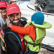 Hamid, cultural mediator of ctionAid Hellas, helps a child to get off the Portuguese coast guard boat at  the fishing harbour of Skala Sykamias, Lesvos, Greece.