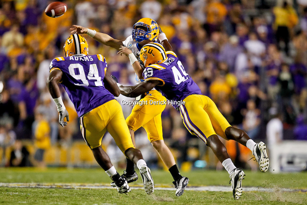 October 16, 2010; Baton Rouge, LA, USA; McNeese State Cowboys quarterback Cody Stroud (18) throws a pass as LSU Tigers defensive end Barkevious Mingo (49) and defensive end Kendrick Adams (94) pursue the play during the second half at Tiger Stadium. LSU defeated McNeese State 32-10. Mandatory Credit: Derick E. Hingle