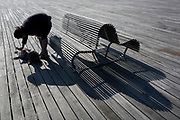 A pet owner bends to tickle her dog with the shadows of a bench on Hastings Pier, on 29th April 2017, at Hastings, East Sussex, England.