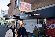 On the last day of the year, people out shopping wearing masks walk past Dorothy Perkins on Kings Heath High Street, as many shops remain closed, with shutters down due to Tier Four coronavirus restrictions on 31st December 2020 in Birmingham, United Kingdom. Small businesses have struggled through the Covid-19 pandemic and many have closed down altogether, as the recession in the economy deepens as the crisis continues.