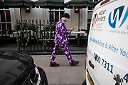 Man wearing a bright colourful suit in pink and purple in Soho, London, United Kingdom.