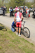 France, April 13th 2014: Team Katusha leader Alexander Kristoff (#61) waits as a mechanic replaces his front wheel by the Pont Gibus during the 2014 Paris Roubaix cycle race.