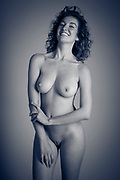 Black and white photo of a beautiful, laughing, sexy nude woman against a gray background laughing